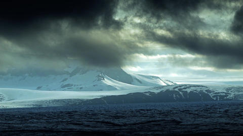 Dark dramatic sunset over snowy mountains Footage