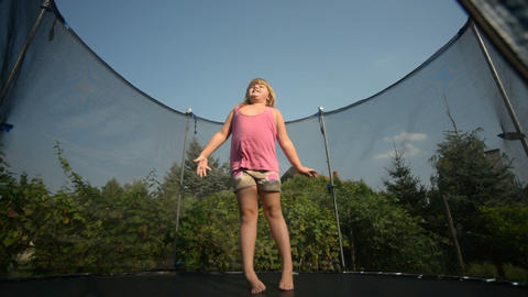 Happy girl jumping in the trampoline Footage