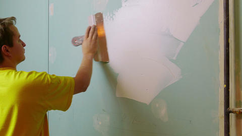 Construction Worker Applying Plaster On A Drywall stock footage