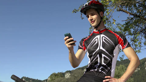 Young Man On Mountain Bike Using Smartphone For Email and Internet GIF