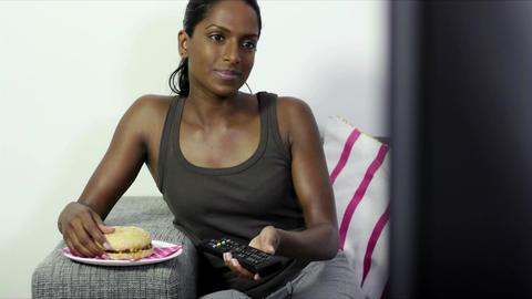 Young Woman Watching Tv And Eating Hamburger At Ho stock footage