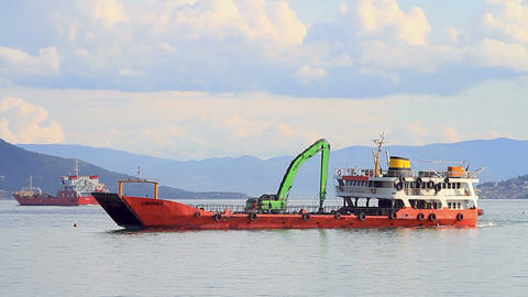 Landing craft sailing into port with an excavator  Footage