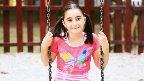 Happy girl on swing smiling at camera Footage