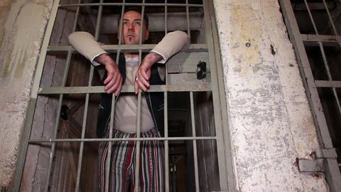 Prisoner standing behind his prison cell door Footage