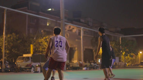 Taiwanese men play night basketball - under hoop a Footage