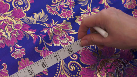 Seamstress Measuring and Marking Fabric Live Action