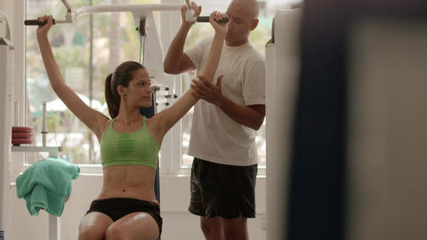 Personal Trainer Helping Young Woman In Fitness Gym Footage