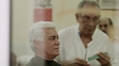 Senior Barber Cutting Hair To Client In Old Fashioned Shop Footage