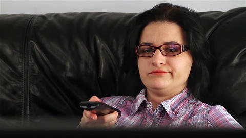 Young woman with remote control watching bored Footage
