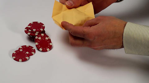 Poker chips fall in origami paper box Footage
