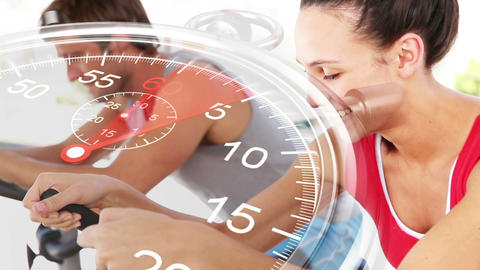 Stopwatch graphic over couple using exercise bikes Footage