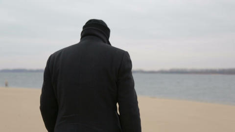 Sad pensive man walks along the shore, close-up Footage