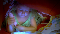 Little girl reading book under covers close up Footage