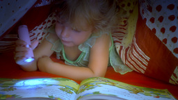 Little girl reading book under covers medium shot Footage