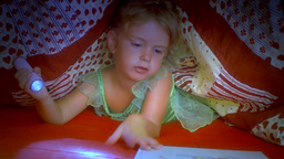 Little girl reading book under covers sleeping Footage