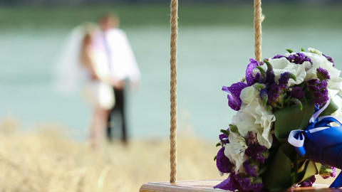 Wedding Bouquet On Seesaw With Blurred Married Cou stock footage