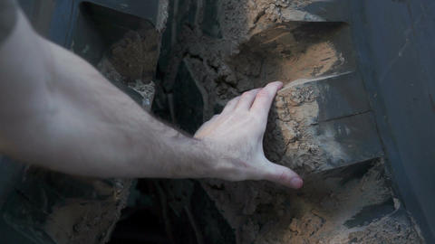 Mechanic Reaches Inspecting Large Tire Live Action