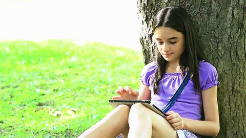 Teenage girl using digital tablet in park Footage