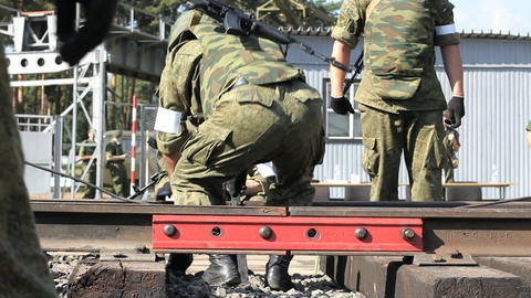 Armed soldiers are fixing railroad Stock Video Footage