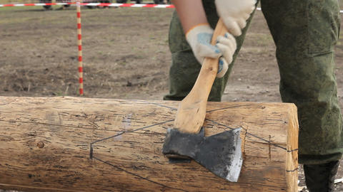 Soldier in camouflage with an ax sharpening log Footage