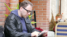 Young man in glasses uses tablet computer Footage
