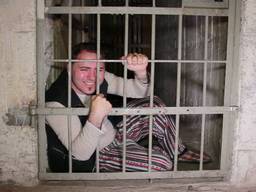 Mad prisioner sits behind a cell bars. Funny Footage