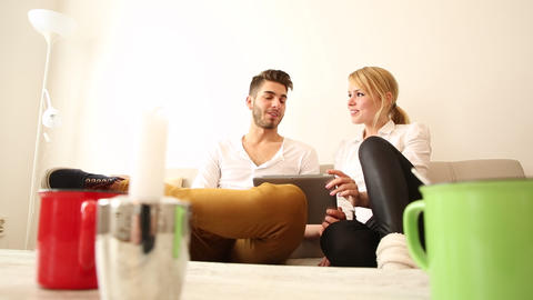 Young couple with a Tablet PC on the Sofa Live Action