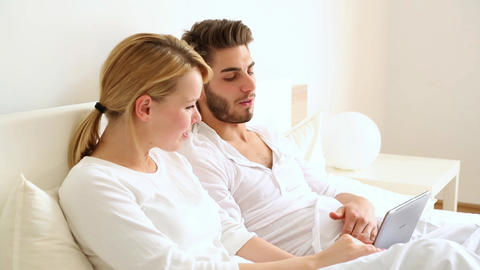 Young couple with a Tablet PC in Bed Live Action