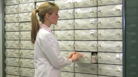 Young woman working as pharmacist in pharmacy, drugstore Footage