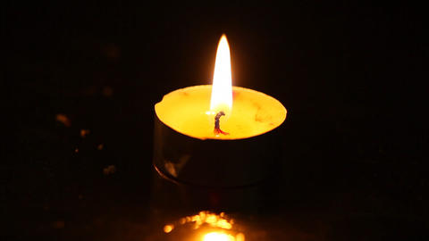 One small burning candle against a black backgroun Footage