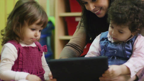 Teacher and little girls playing with iPad digital tablet Footage