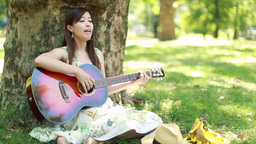 Young Asian Woman Playing Guitar Singing In A Park stock footage