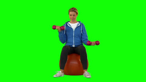 Fit Blonde Sitting On Exercise Ball Lifting Hand W stock footage