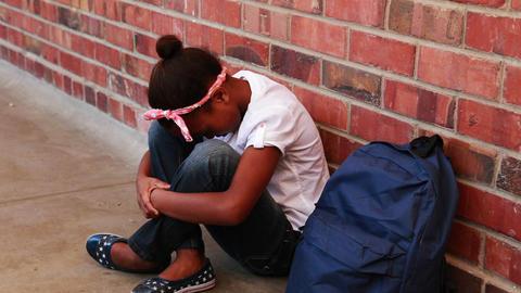 Sad pupil sitting alone in corridor Footage