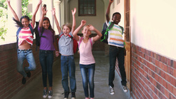 Happy pupils jumping in the air in a hallway Footage