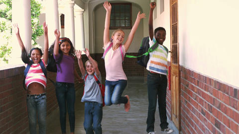 Happy pupils jumping in the air in a hallway Stock Video Footage