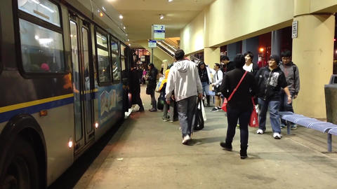 People line up for waiting bus at bus station Live Action