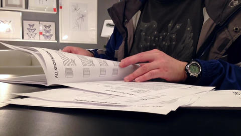 Man reading furniture catalog inside Ikea store Live Action