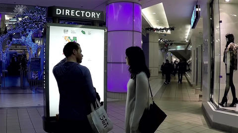 Couple checking store position in front of directo Footage