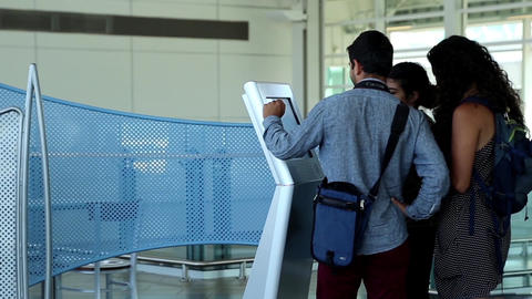People Checking Map At Direction Sign Inside YVR A stock footage