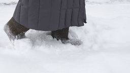 Woman walking in deep snow wearing the felt boots Footage