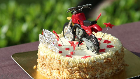 Birthday cake decorated with motorcycle and red st Footage