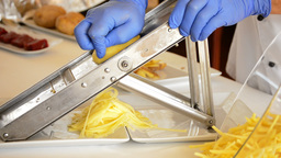 Professional chef hands cutting potatoes with mand Footage