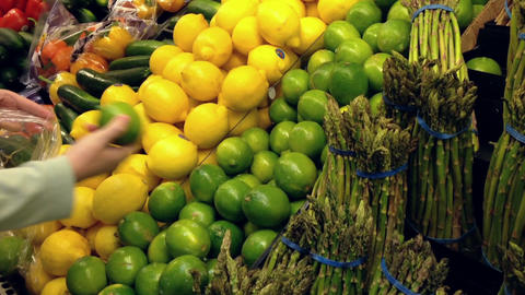 Woman selecting fresh lime in grocery store produc Stock Video Footage