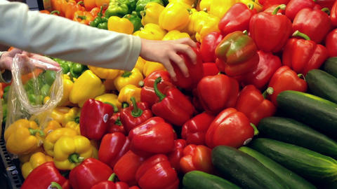 Woman selecting fresh red and yellow peppers in gr Footage