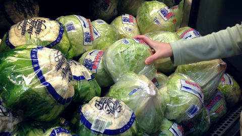 Woman selecting fresh lettuce in grocery store pro Footage
