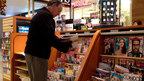 Close up man choosing magazine to buy at newspaper Footage