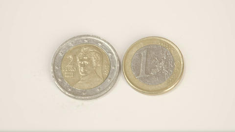A 2 Austian Euro coin and 1 Austria Euro coin on t Live Action