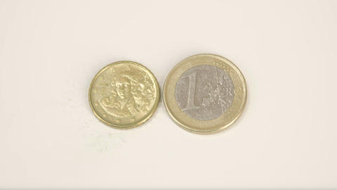 A small gold plated Italy coin and a 1 Euro coin Footage