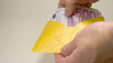 A yellow small envelope with 3 Euro bills Footage
